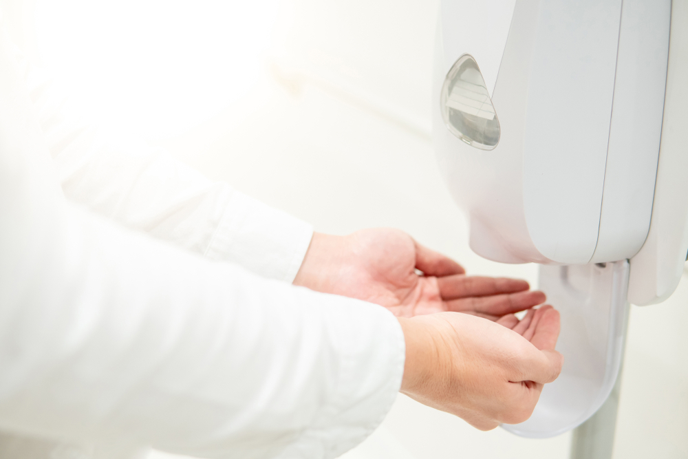 Male patient hands using touch free hand sanitiser dispenser for cleaning hand in the hospital.