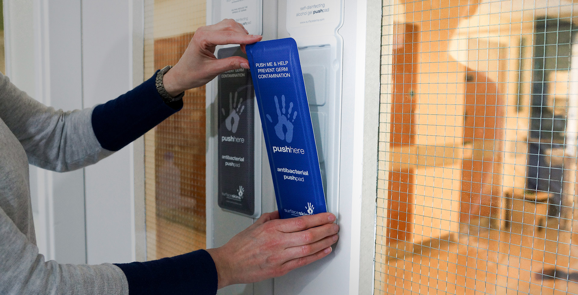 Someone installing Surfaceskins: the door-push disinfectant pads