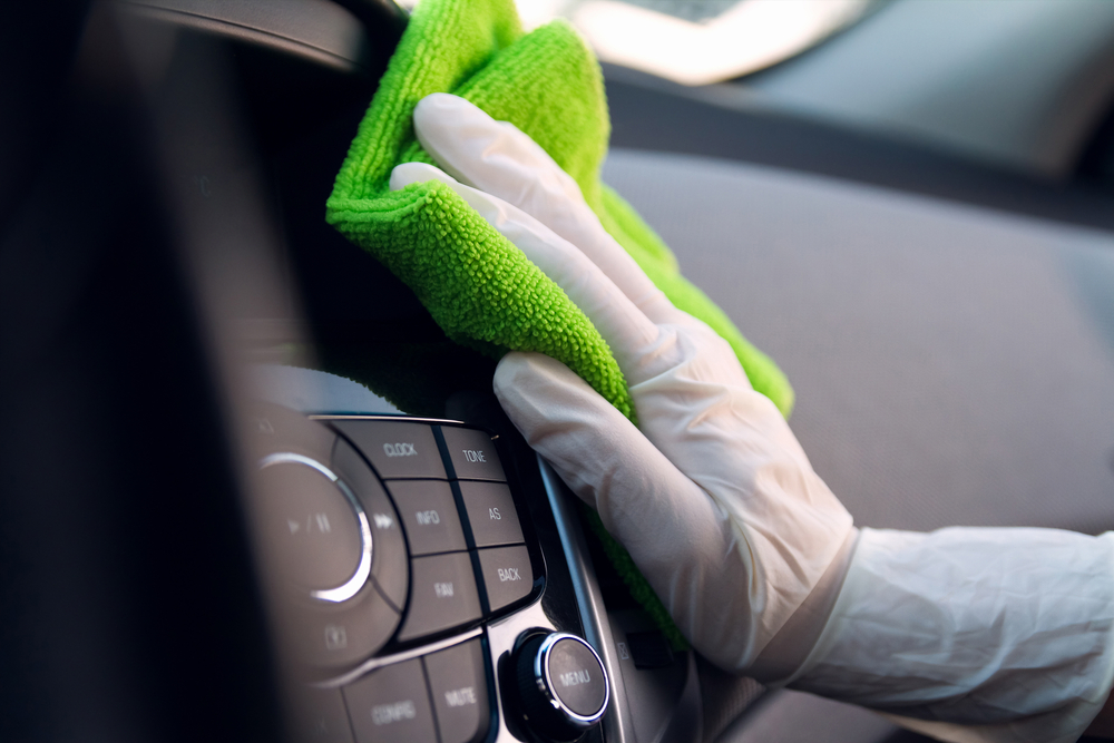 A person using car sanitiser to clean the dashboard of a car